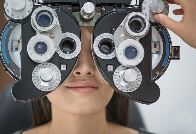 Junges mädchen patientin an der rezeption beim arzt augenarzt diagnostische ophthalmologische geräte