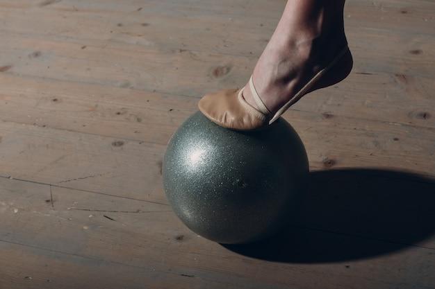 Junges mädchen professionelle turnerin frau bein nahaufnahme rhythmische gymnastik mit ball im studio.