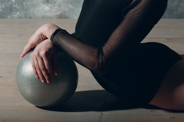 Junges mädchen professionelle turnerin frau tanzt rhythmische gymnastik mit ball im studio.