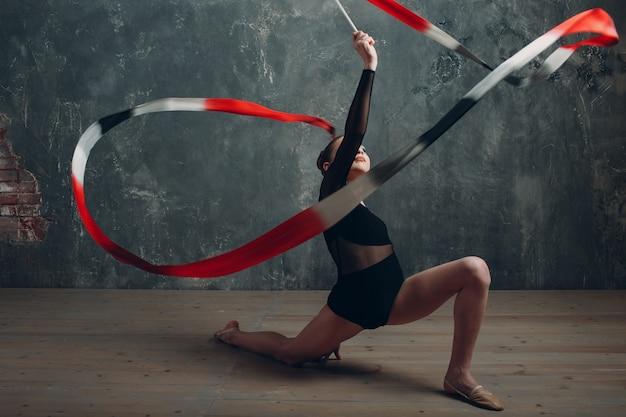 Junges mädchen professionelle turnerin frau tanzt rhythmische gymnastik mit band im studio.