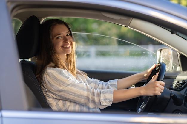 Junges mädchen sitzt am fahrersitz in einem neuen auto und lächelt, hält die hände am rad und freut sich, einen führerschein zu bekommen?