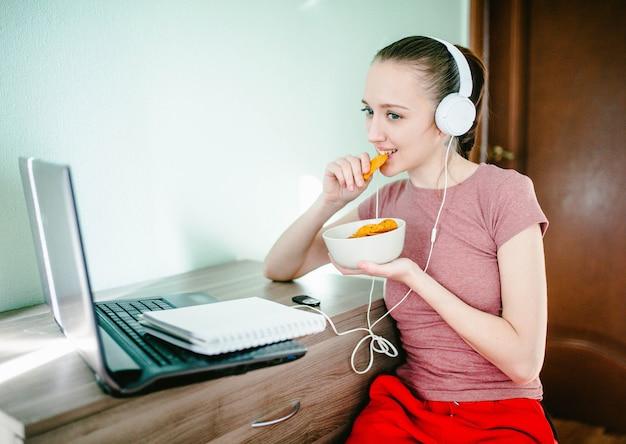 Junges mädchen sitzt an einem laptop in den kopfhörern, lacht und isst chips