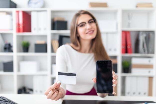 Junges mädchen sitzt an einem tisch und hält ein telefon und eine kreditkarte