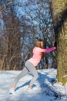 Junges mädchen strebt herein sport im winterpark an.
