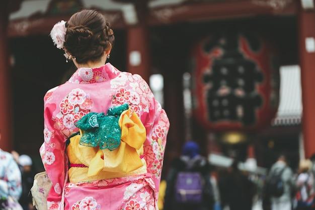 Junges mädchen trägt den japanischen kimono, der vor sensoji-tempel in tokyo steht,
