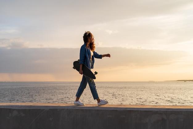 Junges mädchen trägt longboard bei sonnenuntergang mit blick auf das meer stilvolle skateboarder-frau genießt einen spaziergang am meer