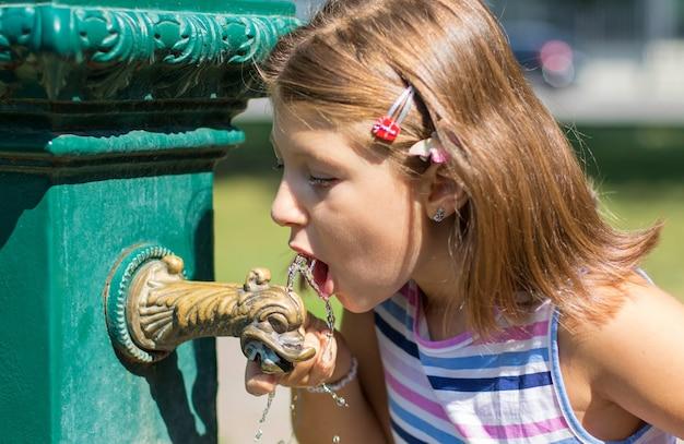 Junges mädchen trinkt aus einem brunnen im park
