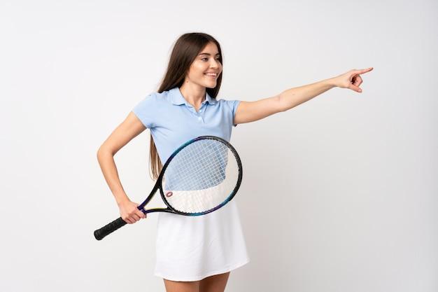 Junges mädchen über der lokalisierten weißen wand, die tennis spielt