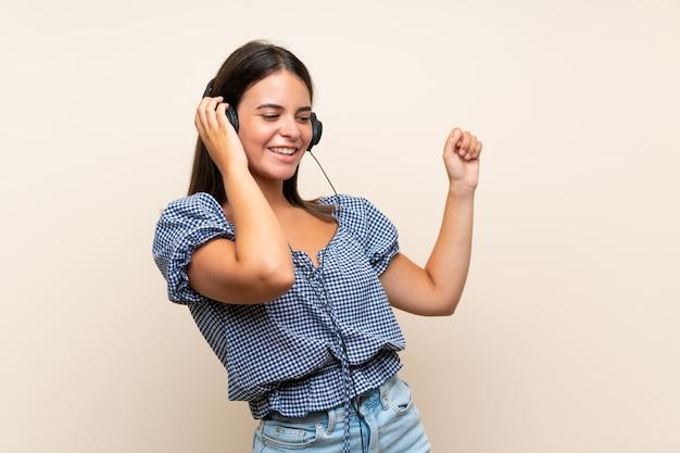 Junges mädchen über lokalisierter wand hörend musik mit kopfhörern