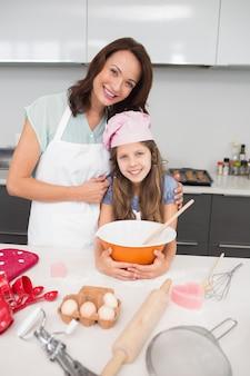 Junges mädchen und mutter, die plätzchen in der küche zubereiten