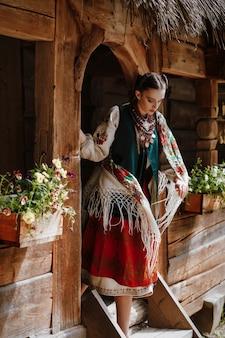 Junges mädchen verlässt das haus in einem traditionellen ukrainischen kleid