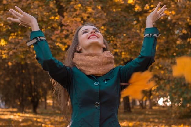 Junges mädchen wirft die blätter im park hoch und lächelt nahaufnahme