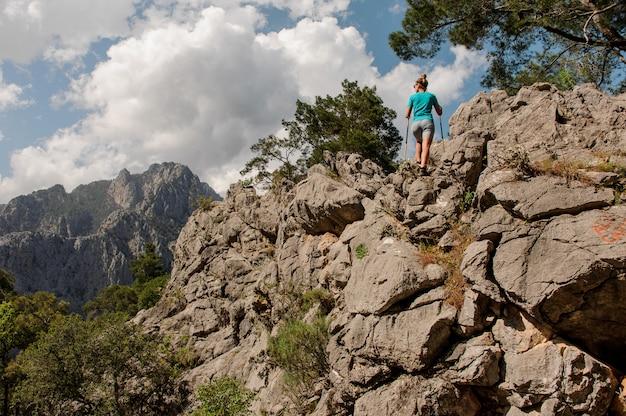 Junges mädchen wirft oben auf den berg auf