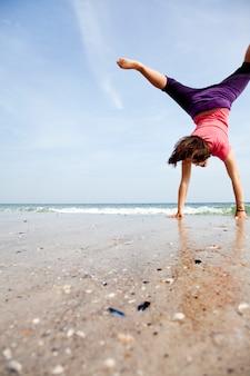 Junges mädchen zeigen eine akrobatische am strand.