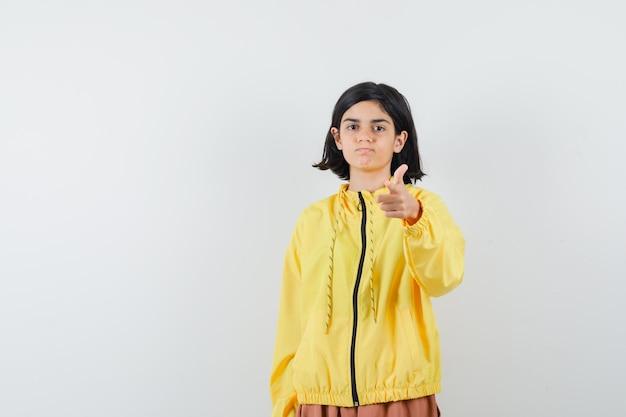 Junges mädchen zeigt auf kamera mit zeigefinger in gelber bomberjacke und rosa rock und sieht ernst aus.