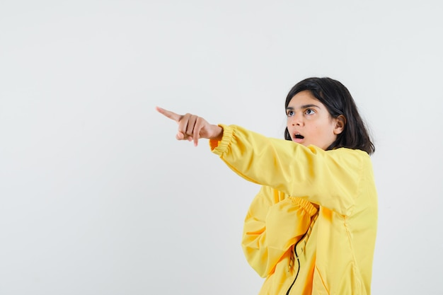 Junges mädchen zeigt linke ecke mit zeigefinger in gelber bomberjacke und sieht überrascht aus.
