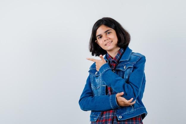 Junges mädchen zeigt nach links, hält die hand am ellbogen in kariertem hemd und jeansjacke und sieht süß aus.