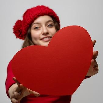 Junges mädchen zeigt rotes pappherz zu einer kamera, valentinstag