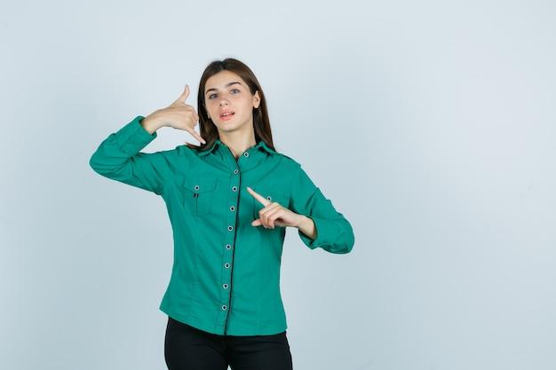 Junges mädchen zeigt telefongeste, zeigt auf die linke seite in grüner bluse, schwarzer hose und sieht zuversichtlich aus. vorderansicht.