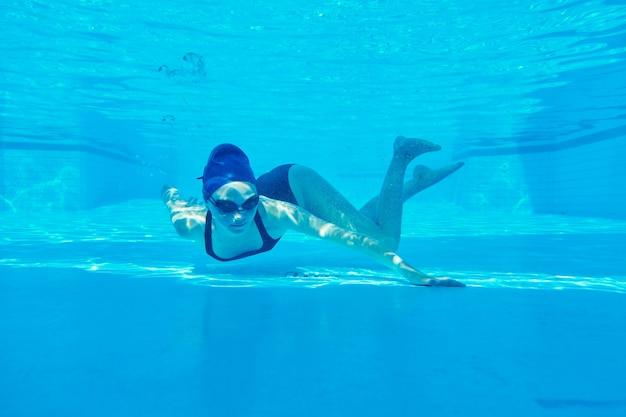 Junges mädchenschwimmer im badeanzug mit schutzbrille und badekappe unter wasser im pool