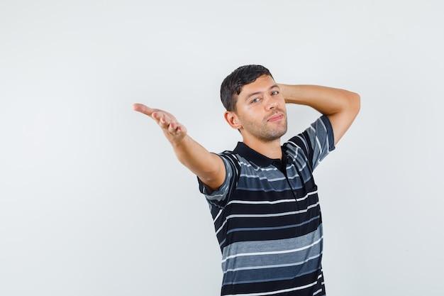 Junges männchen, das die hand mit der anderen hand hinter dem kopf im t-shirt ausdehnt und fröhlich aussieht, vorderansicht.