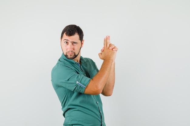 Junges männchen, das eine geste der schusswaffe im grünen hemd zeigt und mutig aussieht, vorderansicht.