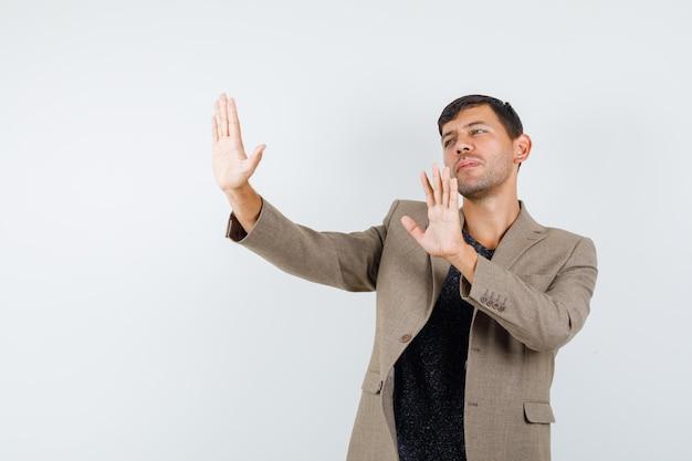 Junges männchen, das eine stopp-geste zeigt, um in graubrauner jacke beiseite zu treten und unzufrieden aussieht, vorderansicht.