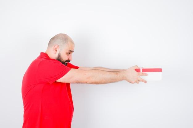 Junges männchen, das geste im roten t-shirt zeigt und süß aussieht. vorderansicht.