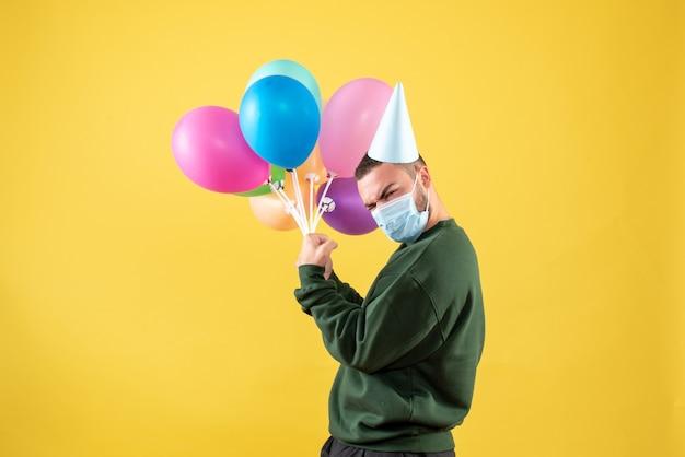 Junges männchen der vorderansicht, das bunte ballons auf gelbem hintergrund hält