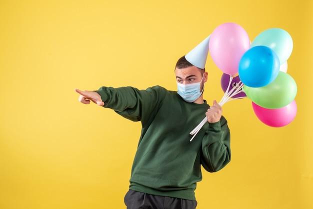 Junges männchen der vorderansicht, das bunte luftballons in maske auf gelbem hintergrund hält
