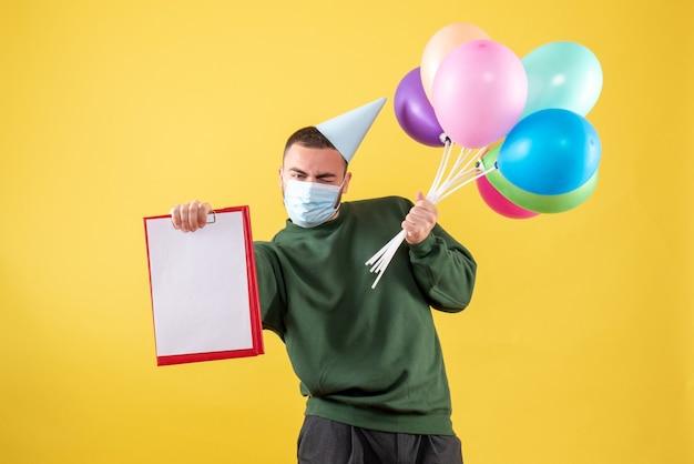 Junges männchen der vorderansicht, das bunte luftballons und anmerkung auf gelbem hintergrund hält