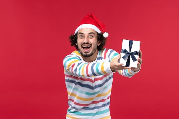 Junges männchen der vorderansicht, das kleines geschenk auf den roten feiertags-neujahrsemotionen des roten hintergrunds hält
