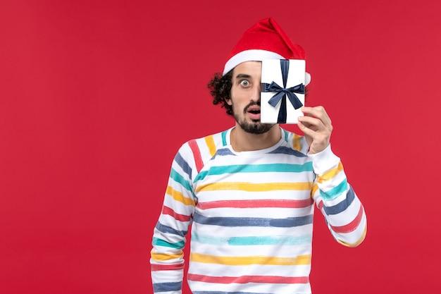 Junges männchen der vorderansicht, das kleines geschenk auf rotem schreibtischfeiertags-neujahrs-gefühlsrot hält