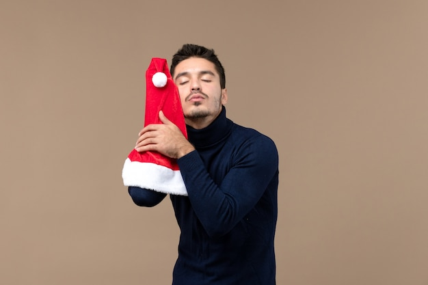 Junges männchen der vorderansicht, das mit roter kappe auf einem braunen hintergrundweihnachtsgefühl neujahr spielt