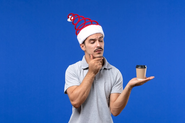 Junges männchen der vorderansicht, das plastikkaffeetasse auf männlichem neujahrsgefühl des blauen bodens hält