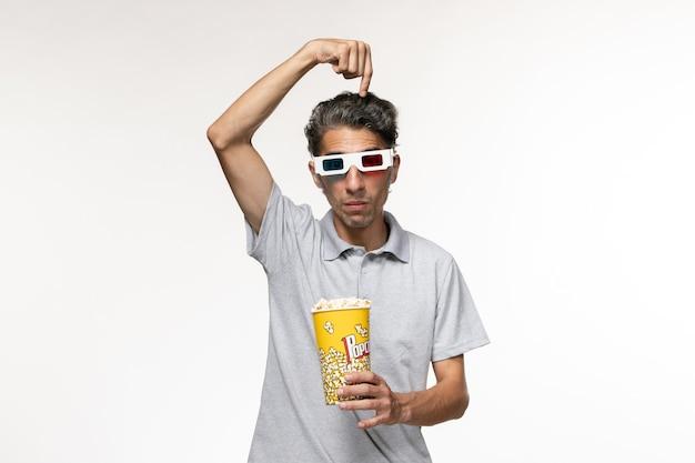 Junges männchen der vorderansicht, das popcorn in d sonnenbrille auf einer hellen weißen oberfläche hält