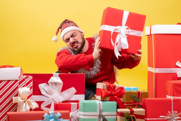 Junges männchen der vorderansicht, das um weihnachtsgeschenke auf gelbem hintergrund sitzt