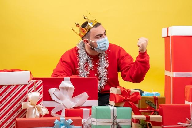 Junges männchen der vorderansicht, das um weihnachtsgeschenke in der maske auf gelbem hintergrund sitzt