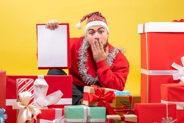 Junges männchen der vorderansicht, das um weihnachtsgeschenke mit hinweis auf gelbem hintergrund sitzt