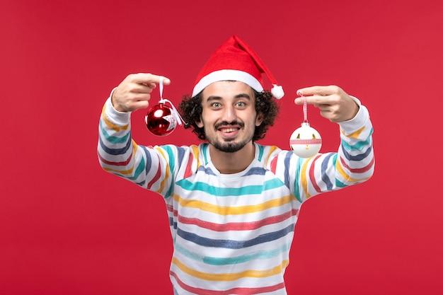 Junges männchen der vorderansicht, das weihnachtsbaumspielzeug auf rotem feiertag des roten schreibtisches neujahr hält