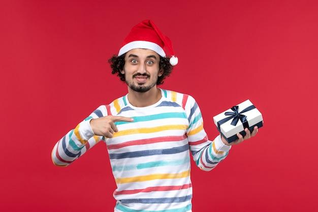 Junges männchen der vorderansicht, das wenig geschenk auf der neujahrsemotion des roten hintergrundfeiertags hält
