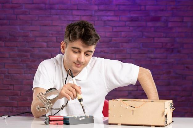 Junges männchen der vorderansicht hinter schreibtisch, das versucht, kleines konstruktionslayout auf lila wand zu reparieren