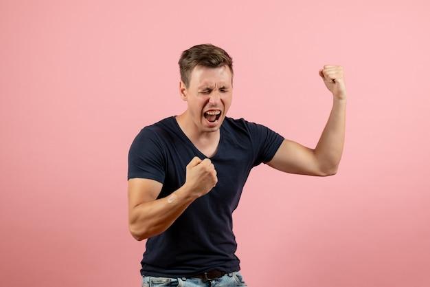 Junges männchen der vorderansicht im dunkelblauen hemd, das sich emotional auf der männlichen menschlichen farbe des rosa hintergrundmannmodells freut