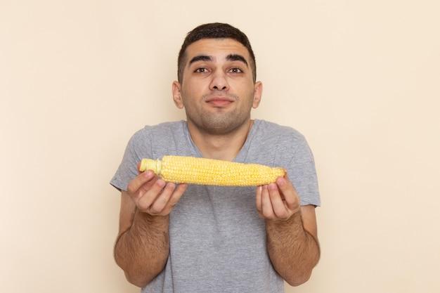 Junges männchen der vorderansicht im grauen t-shirt, das rohen mais auf beige hält