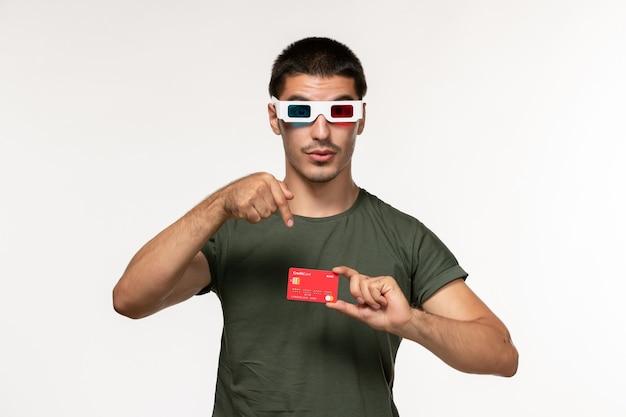 Junges männchen der vorderansicht im grünen t-shirt, das bankkarte auf einsamem kino des weißen wandfilms hält