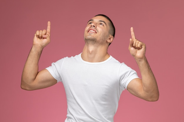 Junges männchen der vorderansicht im weißen t-shirt, das gott auf rosa hintergrund freut und dankt