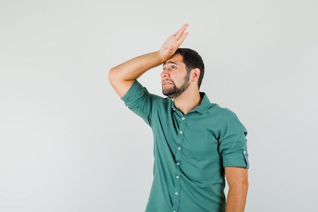 Junges männchen im grünen hemd, das hand auf dem kopf hält und genervt aussieht, vorderansicht.