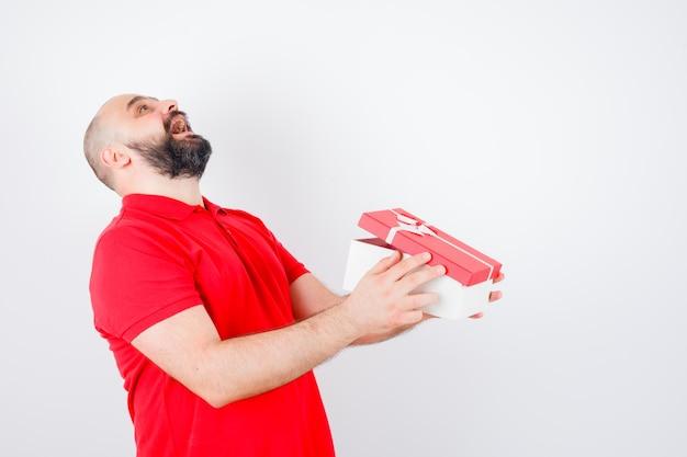 Junges männchen lacht beim halten der geschenkbox im roten t-shirt und sieht glücklich aus, vorderansicht.