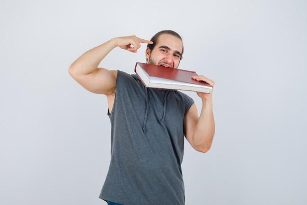 Junges männliches beißbuch beim zeigen auf den kopf im ärmellosen kapuzenpulli und beim glücklichen schauen, vorderansicht.