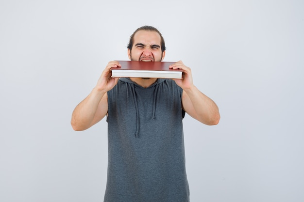 Junges männliches beißbuch im ärmellosen kapuzenpulli, der ausgehungert aussieht. vorderansicht.